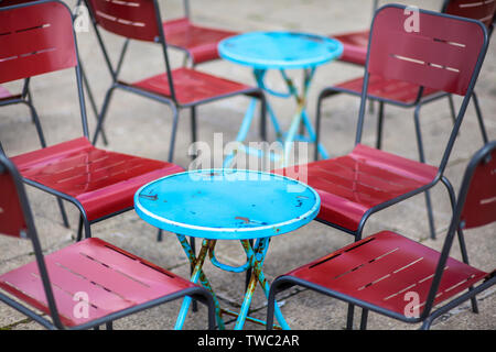 metal blue and red cafe chairs and round tables - Stock Photo