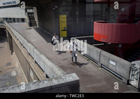 Two women run for their bus along the concrete walkway at the Southbank's Royal Festival Hall, on 15th June 2019, in London, England. - Stock Photo