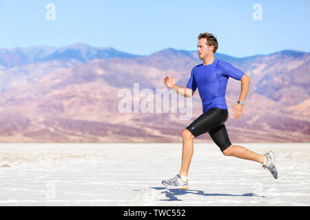 Man running outdoor sprinting for success. Male fitness runner sport athlete in sprint at great speed in beautiful landscape in desert. - Stock Photo