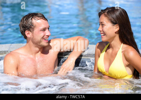 Spa couple happy in wellness hot tub jacuzzi laughing having fun being in love. Happy young lovers on honeymoon vacation travel to luxury resort spa retreat. Handsome man and beautiful asian woman. - Stock Photo