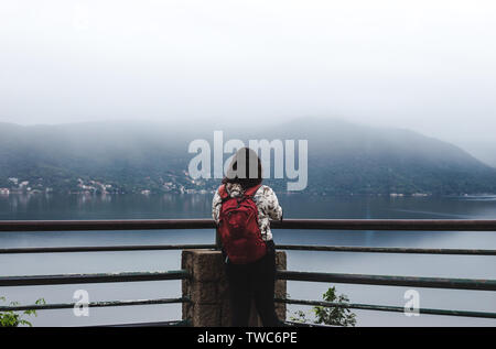 Travel girl backpacker young woman with red backpack at the edge of a misty mountain lake in Florianópolis, Brazil - Stock Photo