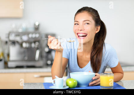 Woman eating breakfast cereals at morning table smiling happy and morning fresh. Beautiful young multiracial woman sitting in her kitchen at home. Mixed race Asian Caucasian female model. - Stock Photo