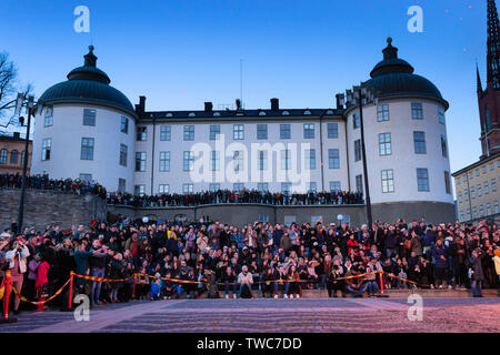 Tourists and local crowds  in front of Wrangel Palace  lit by the burning fire, watching the Mayday eve Valborg custom.Riddarholmen, Stockholm, Sweden - Stock Photo