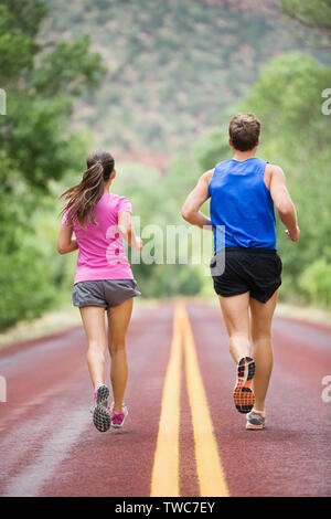 Running training runners jogging on road outside in rear view running away from camera in nature landscape. Sport fitness and healthy lifestyle concept with two people, man and woman. - Stock Photo