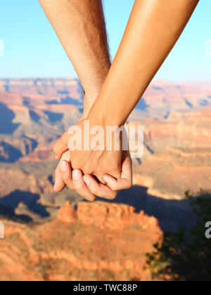 Couple holding hands hiking romantic, Grand Canyon. Close up of young lovers on hike enjoying view and romance. Woman and man hikers.