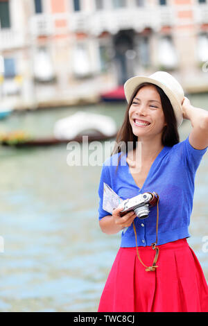 Travel woman tourist traveling in Venice, Italy holding camera and map. Asian girl on vacation smiling happy by Grand Canal. Mixed race Asian Caucasian girl having fun during holidays in Europe. - Stock Photo
