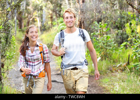 Outdoor activity couple hiking - happy hikers walking in forest. Hiker couple laughing and smiling. Multiracial group, Caucasian man and Asian woman on Big Island, Hawaii, USA. - Stock Photo