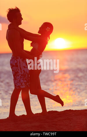 Romantic couple kissing on beach sunset on travel. Happy woman and man embracing in kiss on honeymoon romance in beautiful sun light. Multiracial couple, Image from Big Island, Hawaii. - Stock Photo