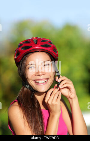 Biking helmet - woman putting bicycle helmet outside. Asian girl on bike, close up of helmet and face. Beautiful mixed race Caucasian Asian female outside. - Stock Photo