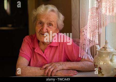 Portrait of an old woman in red clothes sitting at the table. - Stock Photo