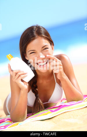 Suntan lotion woman applying sunscreen solar cream laughing having fun. Beautiful happy cute woman asian applying suntan cream from a plastic container to her nose with ocean in background. - Stock Photo