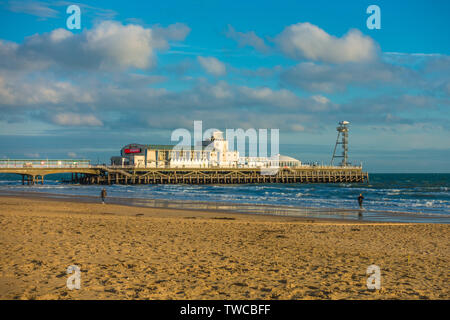 Bournemouth beach and pier, bathed in warm, autumn afternoon sunlight, with just two people on the sand. Dorset, south coast of England, UK. - Stock Photo