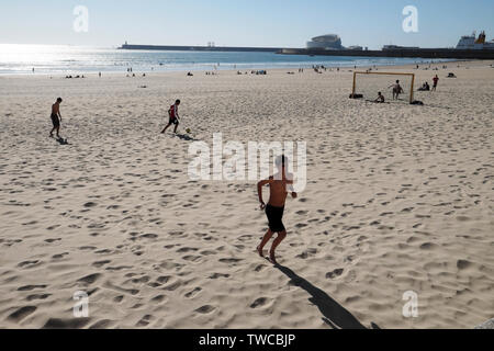 Young people playing football on beach in spring sunshine Matosinhos and view of Port of Leixões & Cruise terminal Porto Portugal Europe KATHY DEWITT - Stock Photo