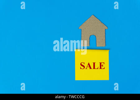 Home for sale. Property sale concept. Real estate sale sign under a small house made by paper cut on blue background. - Stock Photo