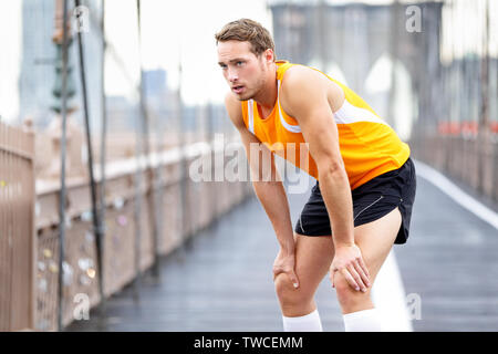 Running man resting after run in New York City. Runner training and jogging outside taking a break. Caucasian male runner and fitness sport model on Brooklyn Bridge, New York City, USA. - Stock Photo