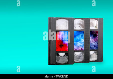 VHS video cassettes on a blue background and colorful stickers - Stock Photo