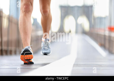 Running shoes, feet and legs close up of runner jogging in action and motion on Brooklyn Bridge, New York City, USA - Stock Photo