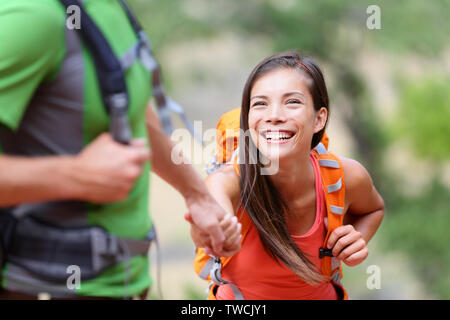 Helping hand - hiking woman getting help on hike smiling happy overcoming obstacle. Active lifestyle hiker couple traveling. Beautiful smiling mixed race Asian Caucasian female model.