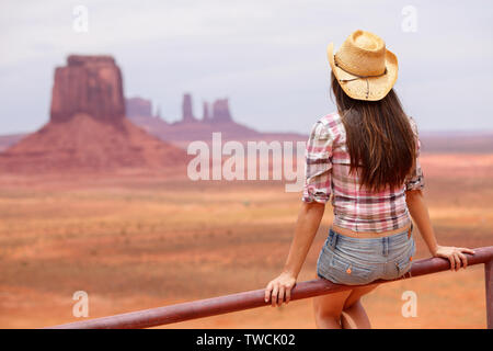 Cowgirl woman enjoying view of Monument Valley wearing cowboy hat. Beautiful young woman on sitting looking outdoors, Arizona Utah, USA. - Stock Photo