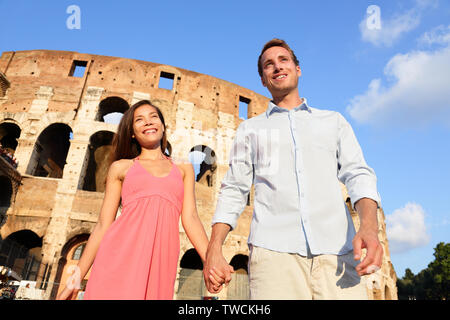 Couple in Rome by Colosseum walking holding hands in Italy. Happy lovers on honeymoon sightseeing having fun in front of Coliseum. Love and travel concept with multiracial couple. - Stock Photo