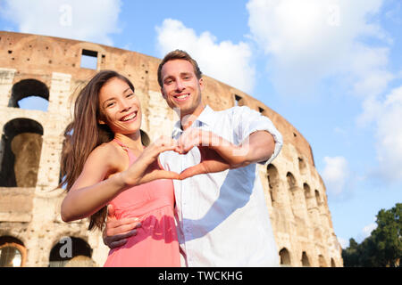 Romantic travel couple in Rome by Colosseum, Italy. Happy lovers on honeymoon showing heart sharped hands having fun in front of Coliseum. Love and travel concept with multiracial couple. - Stock Photo