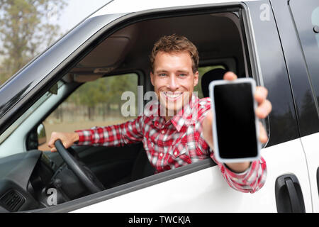 Smartphone man in car driving showing smart phone display smiling happy. Male driver using app showing blank empty screen sitting in drivers seat. Focus on model. - Stock Photo