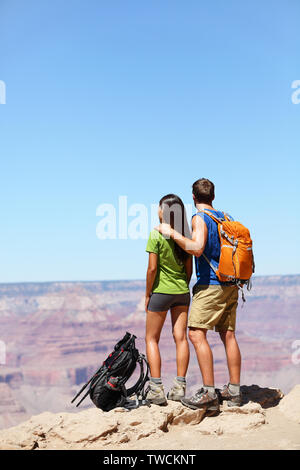 Hikers in Grand Canyon - Hiking couple looking at view. Hiker man and woman enjoying view of nature landscape wearing backpacks. Young couple relaxing after hike in Grand Canyon, Arizona, USA - Stock Photo