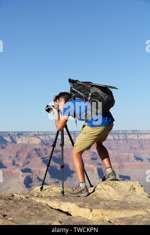 Nature landscape photographer in Grand Canyon taking picture photos with SLR camera and tripod during hike on south rim. Young man hiker enjoying landscape in Grand Canyon, Arizona, USA. - Stock Photo
