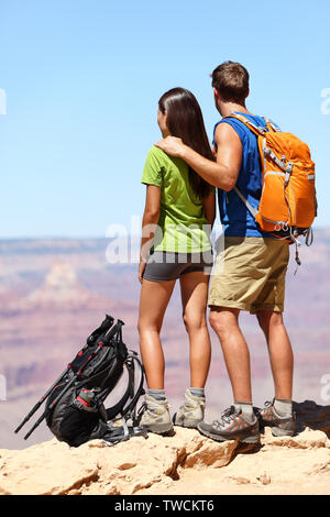People hiking - Hikers in Grand Canyon. Hiking couple looking enjoying at view of nature landscape wearing backpacks. Young man and woman hiker relaxing after hike in Grand Canyon, Arizona, USA - Stock Photo