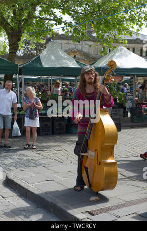 Street Musician performing a solo segment on his stand-up bass on market day in Wells, Somerset, UK - Stock Photo