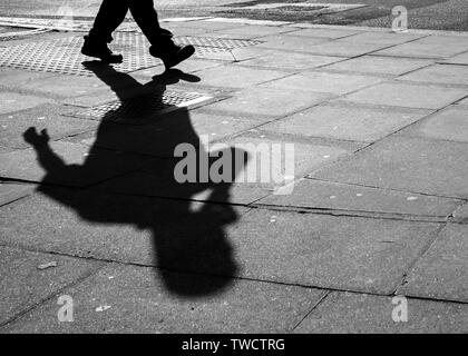 Pavement Shadow of a Person Using a Cell Phone. abstract. - Stock Photo