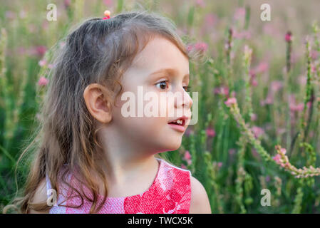 Cute baby girl looks aside outdoors in green field. Child portrait - Stock Photo