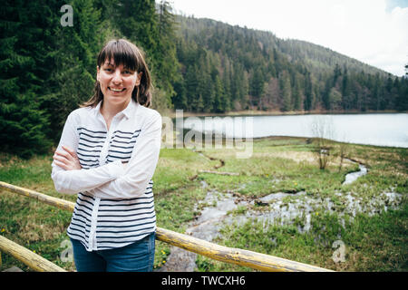 Tourist girl in blue jeans and striped shirt standing on the bank of the mountain lake surrounded by forest. Travel concept. - Stock Photo