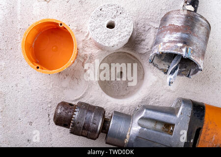 Drill for drilling large holes in the wall. Device for making holes for electrical sockets. Place - workshop. - Stock Photo