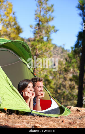 Camping couple in tent romantic looking at view in forest. Campers smiling happy outdoors in forest. Multiracial couple having fun relaxing after outdoor activity. Asian woman, Caucasian man. - Stock Photo