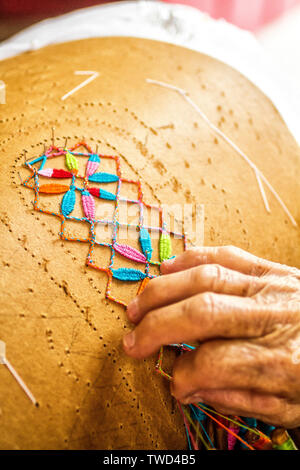 Hands of an artisan woman doing bobbin lace work in Sambaqui, at Santo Antonio de Lisboa district. Florianopolis, Santa Catarina, Brazil. - Stock Photo