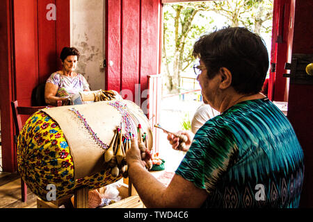 Artisan women doing bobbin lace work in Sambaqui, at Santo Antonio de Lisboa district. Florianopolis, Santa Catarina, Brazil. - Stock Photo