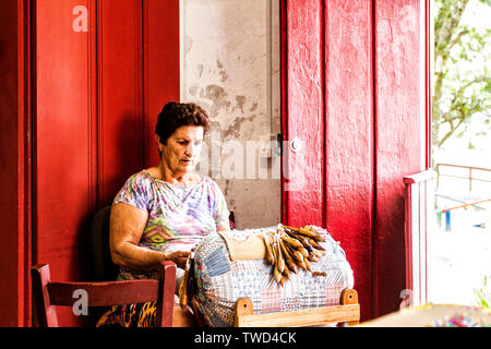 Artisan woman doing bobbin lace work in Sambaqui, at Santo Antonio de Lisboa district. Florianopolis, Santa Catarina, Brazil. - Stock Photo