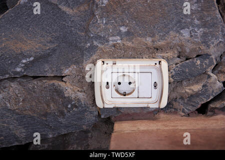 Image of an aged plug placed in a rustic stone wall with space to the left to add some graphic element - Stock Photo