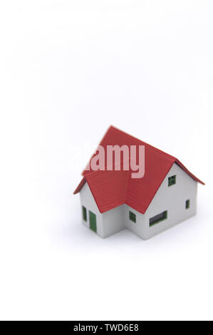 A small house with traditional red roof on a white surface and space to add other graphic elements as well as texts. - Stock Photo