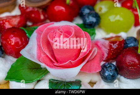 cake decoration of cakes with a layer of cream decorated with fruit in gel and rose flower of sugar paste close-up. - Stock Photo