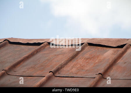 Rusty corrugated metal roof against a blue sky, soft focus, copyspace - Stock Photo