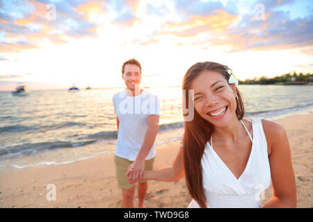 Happy couple on beach holding hands at sunset in romantic walk at night during honeymoon summer vacation travel holidays. Multi-ethnic couple, young Asian woman and Caucasian man. - Stock Photo