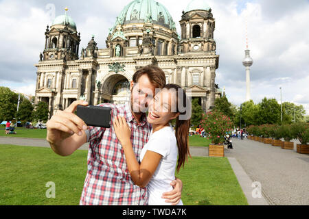 Berlin Germany travel couple selfie self portrait. Happy tourists people in front of Berlin Cathedral / Berliner Dom with Fernsehturm / Berlin TV Tower in the background. Asian woman, Caucasian man. - Stock Photo