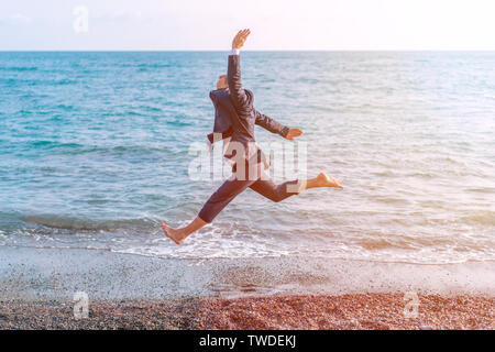 Happy businessman jumping on the beach. Man having fun by the sea. Summer vacation and travel concept - Stock Photo