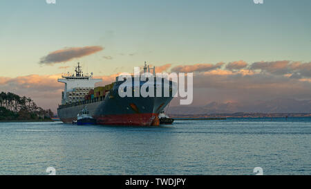 Two pilot vessels nudge a container ship through the cut and into Port Nelson, New Zealand. - Stock Photo