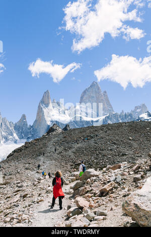 Hikers trekking up hill and looking at epic mountain scenic view on trail to Mount Fitz Roy in Patagonia, Argentina - Stock Photo