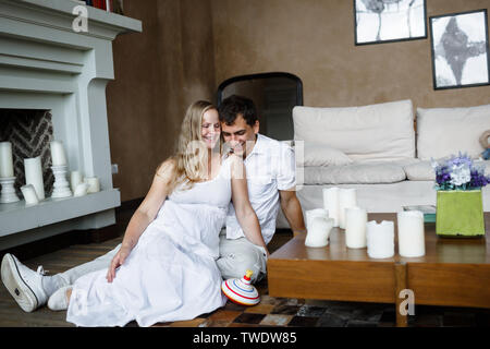 Lovely young happy couple in white clothes sits on a floor hugging and laughing, the girl is pregnant - Stock Photo