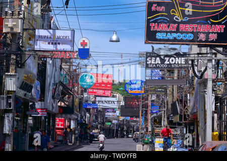 Notorious entertainment area Walking Street, Pattaya, Thailand, full of signboards advertising bars, and looking fairly unglamorous in bright daylight - Stock Photo