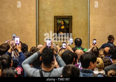 Paris, France, Oct 07, 2018 Louvre Museum, tourists using cameras, mobile phones over heads, taking pictures Mona Lisa La Gioconda Leonardo da Vinci - Stock Photo